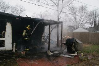 Firefighter Tory Routier sprays hot spots during a house fire